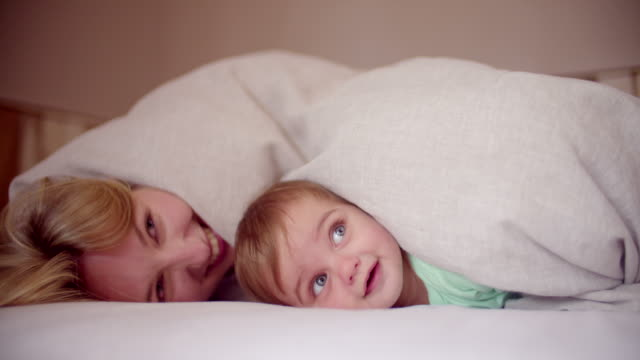 Baby boy and his mother palying together at home video