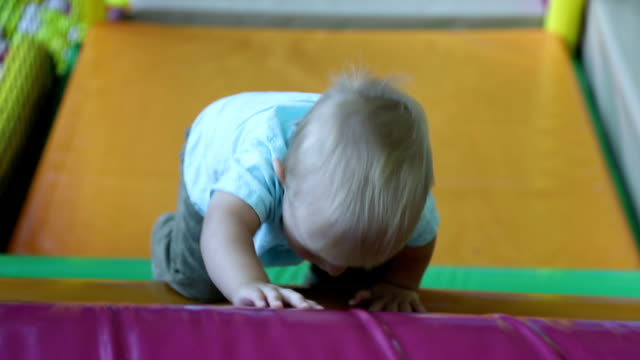 baby boy climbs the wall with obstacles in children's entertainment center. slow motion - solo neonati maschi video stock e b–roll