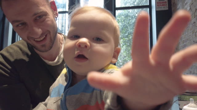 baby boy eating from father's hand - nazionalità russa video stock e b–roll