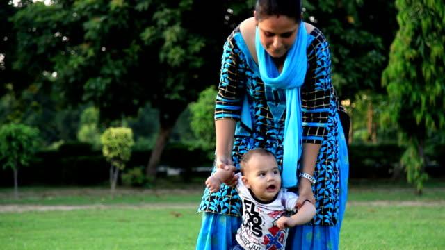 baby pojke första steg med sin mor - enbarnsfamilj bildbanksvideor och videomaterial från bakom kulisserna