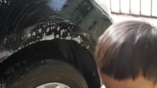 Baby boy help his mother for washing the car at home, 4K