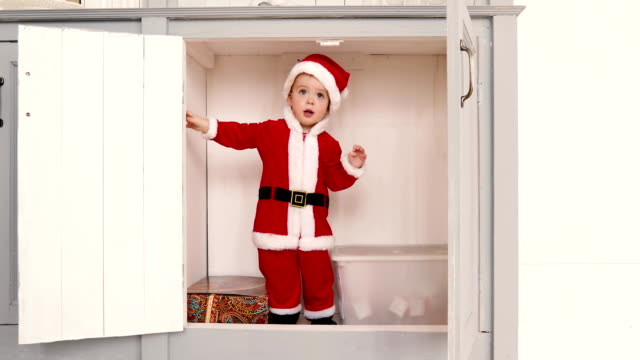 Baby boy in a Santa suit opens closet from inside video