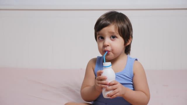 baby boy in blue t-shirt sitting on the bed at home and drinking milk
