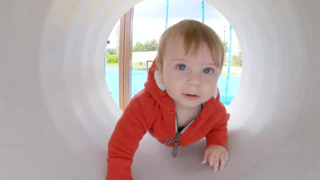baby boy in the tube - scivolo video stock e b–roll