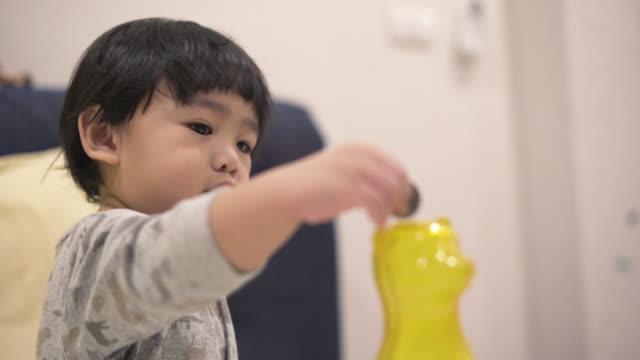 baby boy inserting a coin - solo neonati maschi video stock e b–roll