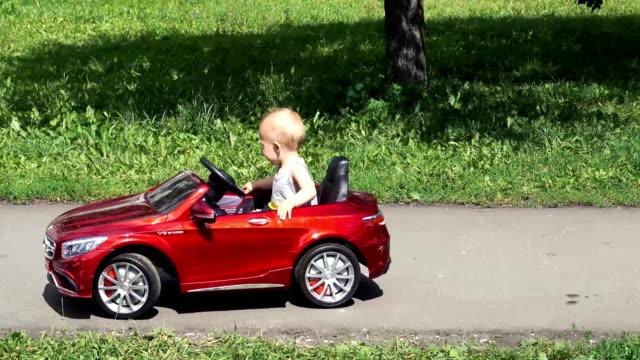 stockvideo's en b-roll-footage met babyjongen rijdt een speelgoedauto gedreven door vader - baby toy