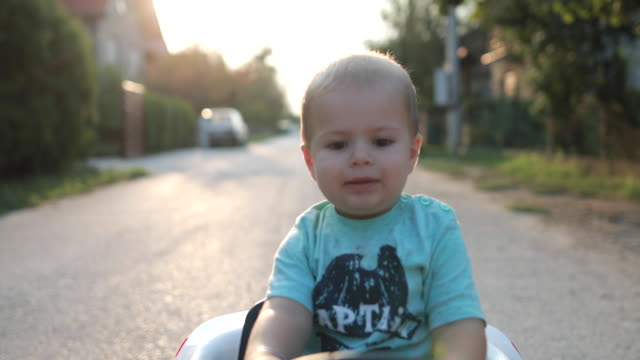 Baby Boy Learning To Drive Cute Baby Boy Learning To Drive His New Toy Car In His Street boys stock videos & royalty-free footage