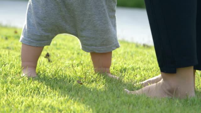 baby pojke att lära sig gå på grönt gräs och gör sin första steg och mor håller sin hand - på tå bildbanksvideor och videomaterial från bakom kulisserna