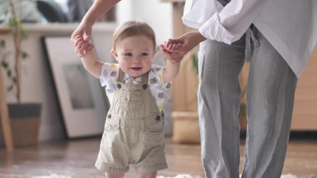 vídeos y material grabado en eventos de stock de bebé niño aprendiendo a caminar niño dando los primeros pasos con la madre ayudando en casa - principios