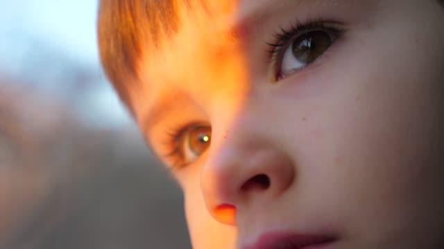 un bambino che guarda dalla finestra. il bambino viaggia su un treno. faccia da adolescente da vicino. traffico ferroviario. alba mattutina. viaggiare in treno. comodo trasporto ferroviario. faccia che si riflette nel vetro, nella finestra. - passare davanti video stock e b–roll