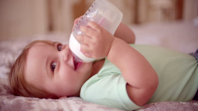 Baby boy lying down and drinking from a bottle video