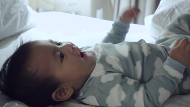 vidéos et rushes de 4k: petit garçon couché sur le dos et le rire - allongé sur le dos