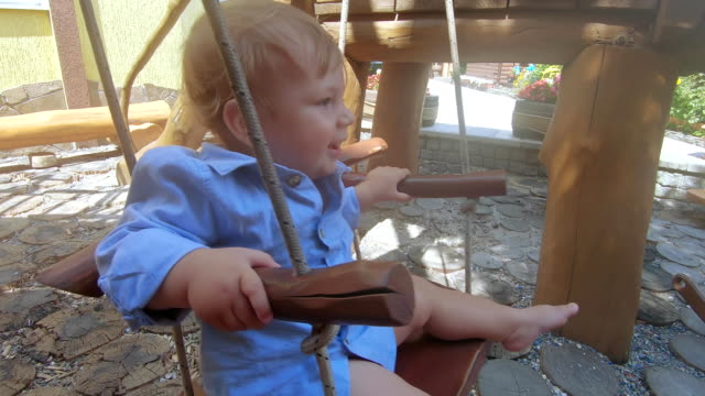 Baby boy on a wooden swing Near doll wooden cabin boy child swinging on a wooden swing rocking chair stock videos & royalty-free footage