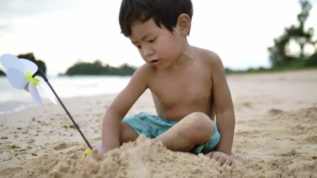 Baby boy play sand on the beach