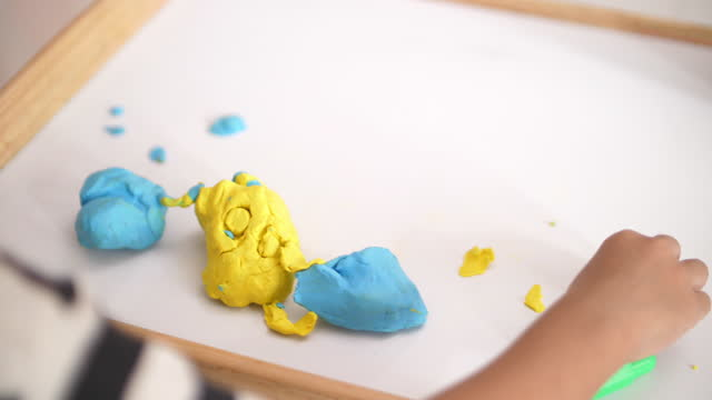 Baby boy playing and create plasticine follow his idea