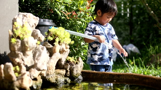 Baby boy playing around fish pond. video