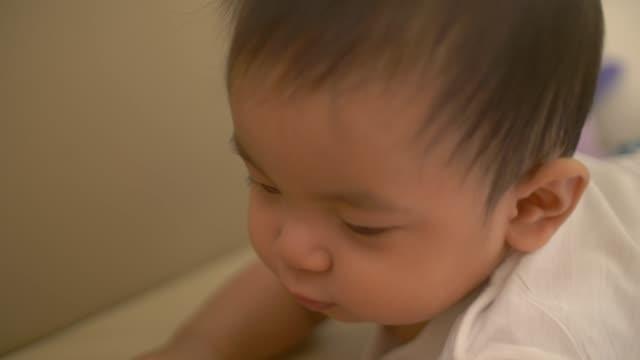 baby boy playing on sofa - abbigliamento da neonato video stock e b–roll