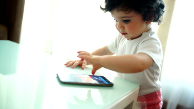 Baby boy playing with a smartphone.