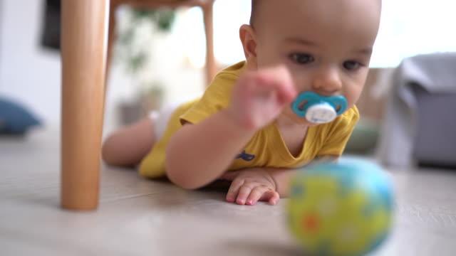 stockvideo's en b-roll-footage met baby jongen spelen met zijn favoriete speeltje op de vloer - baby toy