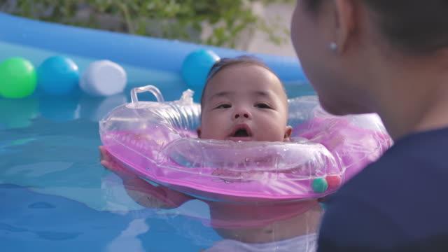 ホームの前庭の庭でボールのおもちゃで水に浮かぶスイミングプールで母親と遊ぶ赤ちゃんの男の子 ビデオ