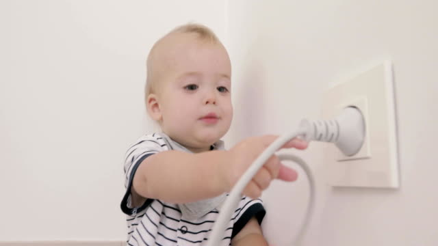 Baby boy playing with plug and socket video
