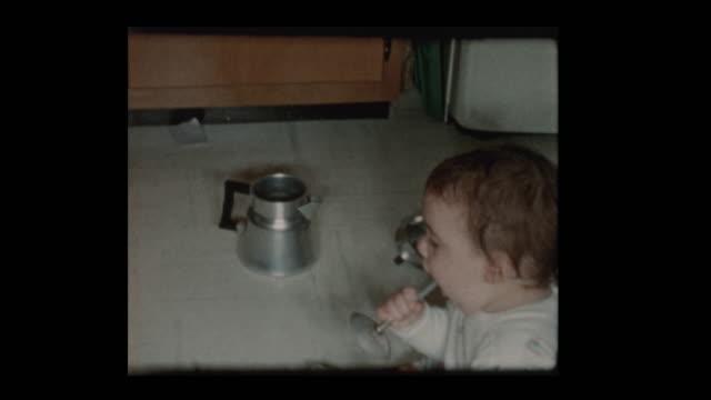 1960 baby boy plays with antique coffee percolator - hotel reception filmów i materiałów b-roll