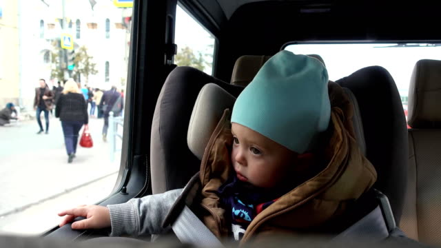 Baby boy sits in car on chair by city streets video