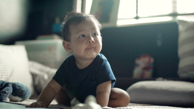 A baby boy sitting and crawling on a bed indoors video