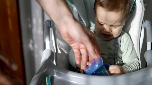 Baby Junge sitzen im Hochstuhl Trinkwasser – Video