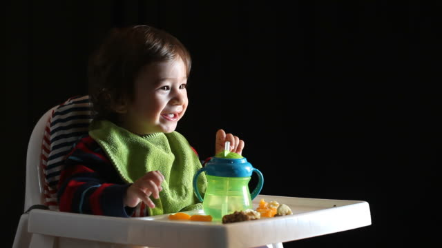 Baby boy sitting on high chair and eating fruits video