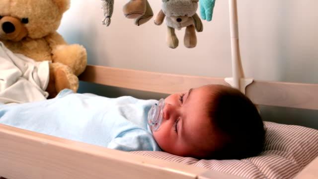 baby boy sleeping in crib - baby sleeping bildbanksvideor och videomaterial från bakom kulisserna