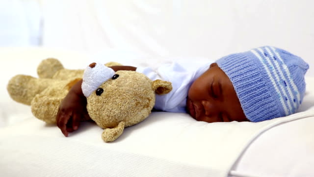Baby boy sleeping in crib with teddy bear video