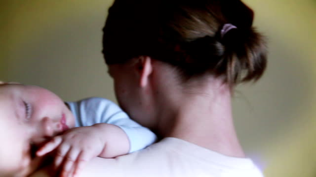 Baby boy sleeping in mother arms, panning video