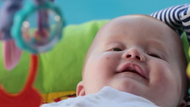 vidéos et rushes de petit garçon souriant sur tapis de bébé - 0 11 mois