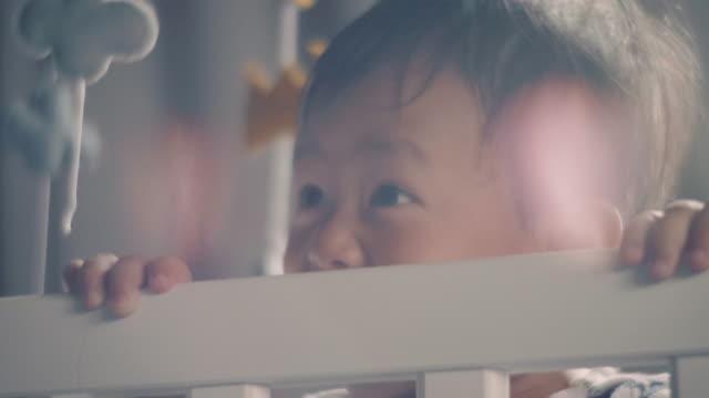 stockvideo's en b-roll-footage met babyjongen permanent en lachen in wieg thuis. - baby toy