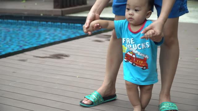 bebek çocuk (6-11 ay) alarak ilk adımları - uzun adımlarla yürümek stok videoları ve detay görüntü çekimi