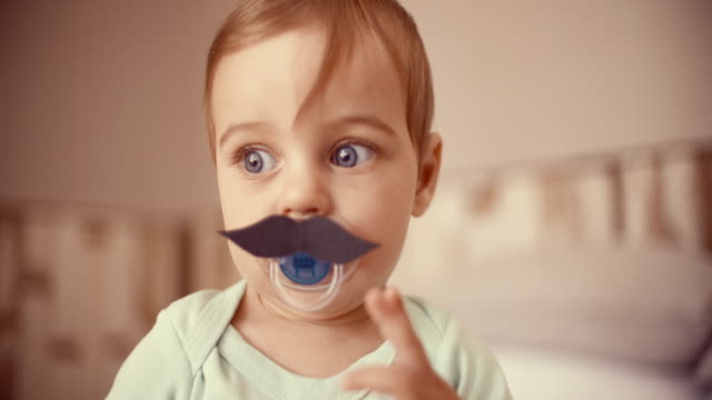 Baby boy touching a moustache that's stuck onto his pacifier video