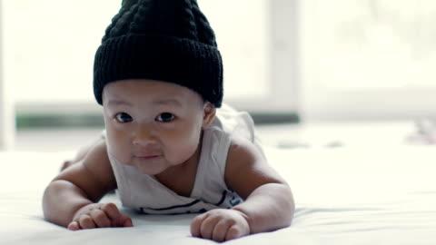 bambino (6-9 mesi) indossare cappello con strisciare sul tappetino - carino video stock e b–roll