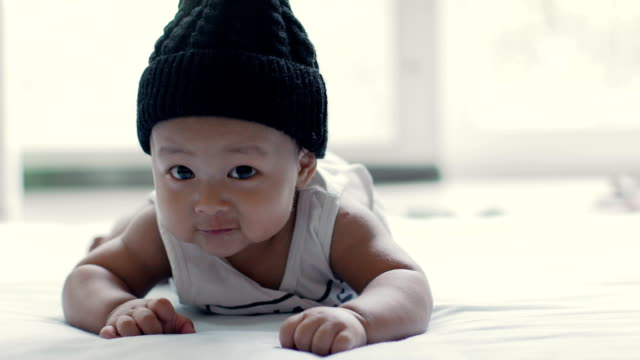 Baby boy (6-9 months) wear hat with crawling on the mat видео