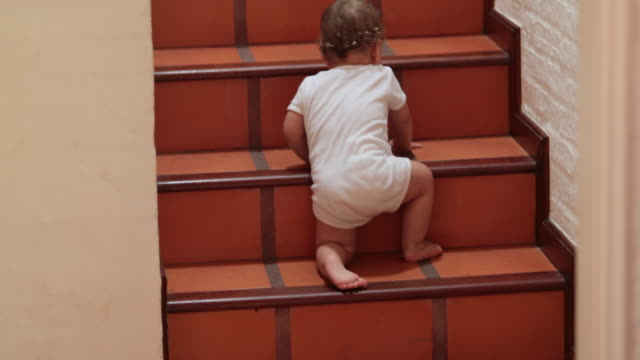 Baby climbing and standing on home stairs