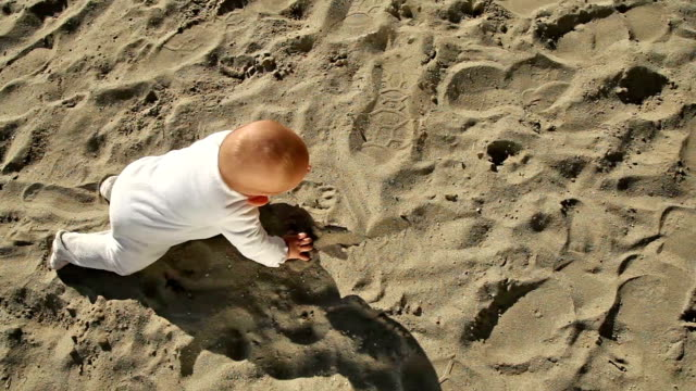 Baby crawling on sand, steadicam above video