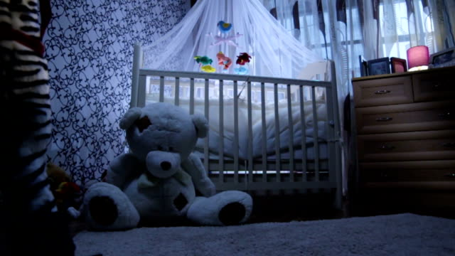 vídeos de stock e filmes b-roll de baby crib stands near toy bear in room - animal doméstico