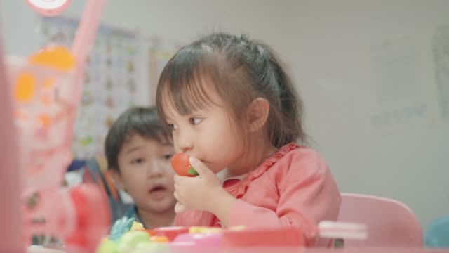 Baby cute girl with cooking utensil while playing with her brother video