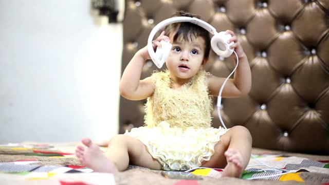 Baby daughter listening music by using headphone video