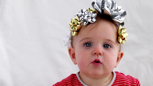 baby decorated with a bow as a gift - nastro per capelli video stock e b–roll