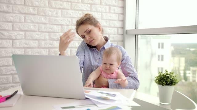 baby abgelenkt mutter aus dem gespräch. moderne frau, die von zu hause aus arbeiten - hart arbeiten stock-videos und b-roll-filmmaterial