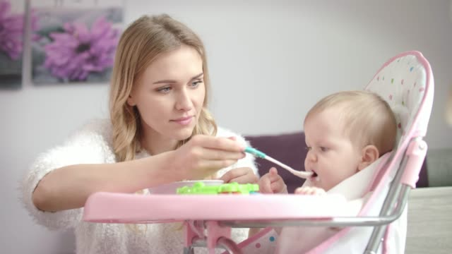 Baby don't want eating food. Mother feeding child with porridge Baby don't want eating food. Mother feeding child with porridge. Little baby not eating. Mother care. Little kid eating from bowl spoon stock videos & royalty-free footage