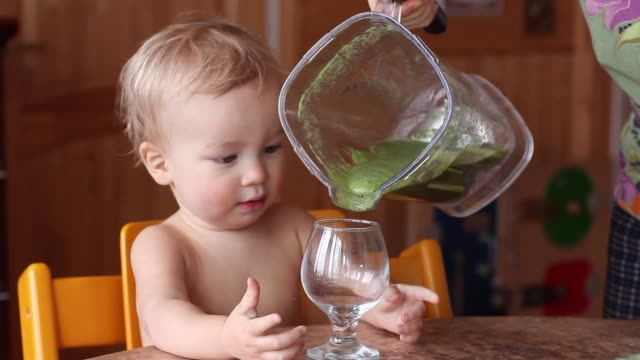 baby drinks fresh green smoothie from wineglass. healthy vegan/raw lifestyle. mother fills wineglass. - healthy green juice video stock e b–roll