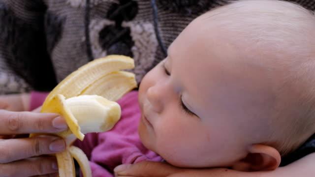 母の手からバナナを食べる赤ちゃん - ローフード点の映像素材/bロール