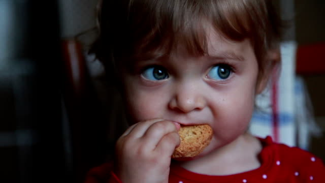 Baby eating cookie Close-up of a baby girl eating dry bread and looking down, playing with mobile phone cookie stock videos & royalty-free footage